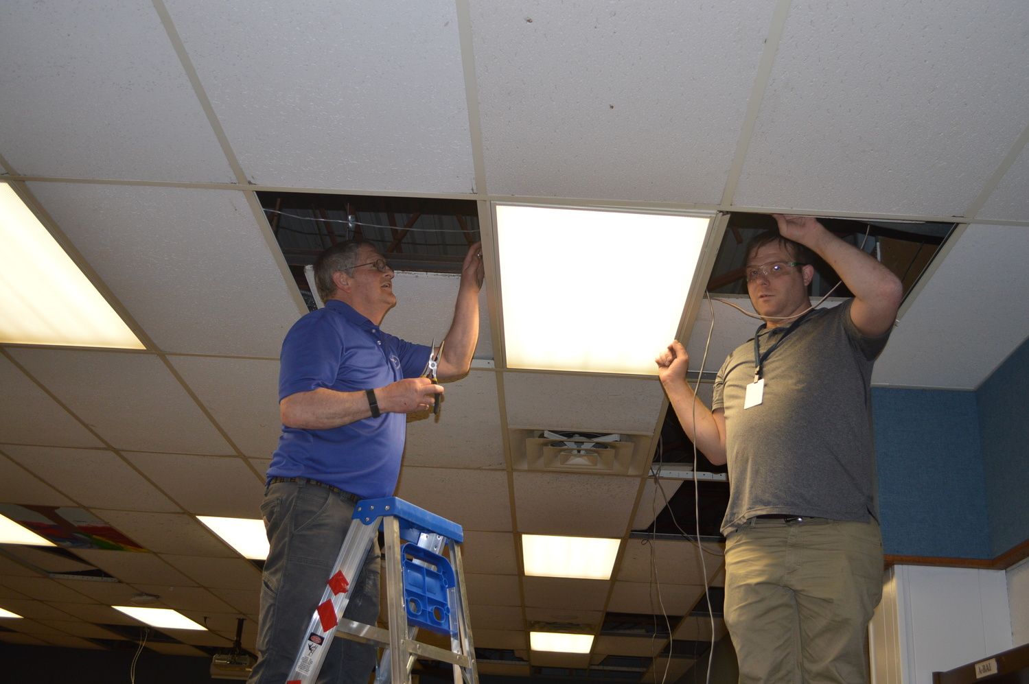 Tom Young and Chris Tipton installing hearing loop wire above the ceiling.